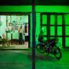 Photo 16 : Ein alter Mann steht in Bago  in seinem Zimmer hinter dem grün erleuchteten Vorplatz, Burma_Myanamar, 2012 © Werner Mansholt
