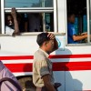Photo 6 : Aus einem anhaltenden Bus in Yangon schaut ein Mann auf vorbeilaufende Männer, Burma_Myanamar, 2012 © Werner Mansholt