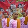 Photo 4: Junge Nonnen stehen in rosa Kleidung vor einem Werbeplakat in Yangon, Burma_Myanamar, 2012 © Werner Mansholt