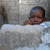 Photo 5: Ein Junge schaut über die Mauer aus Korallenstein, Jambiani, Sansibar 2008  © Werner Mansholt
