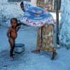Photo 10: Eine Mutter wäscht ihr Kind in Nungwi, Sansibar 2008  © Werner Mansholt