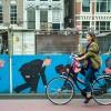 Photo 7: Eine Radlerin passiert den beklebtenZaun an der Baustelle der neuen U-Bahn, Amsterdam 2013 © Werner Mansholt