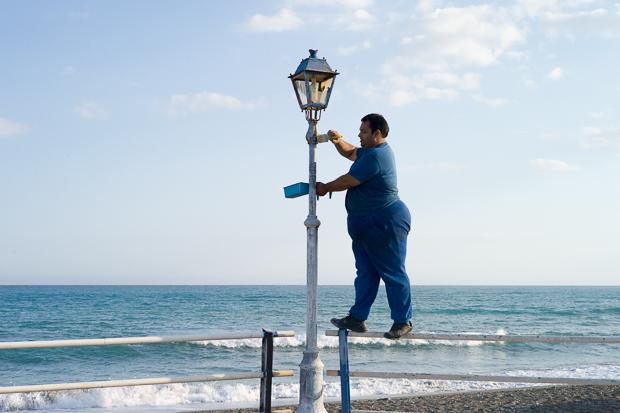 Ein Mann streicht eine Laterne am Meer an, Gra Lia, Kreta, Griechenland